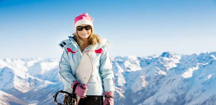 Female Ski Resort Employee Poses with Snowboard