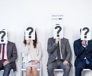 Job candidates waiting for job interview while holding question marks over face